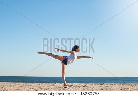 Young woman performing yoga on the beach during a beautiful morning. Beautiful young woman stretching during yoga on the beach. Young woman balancing on one leg in yoga stretch position at the beach.