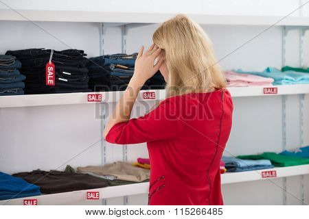 Confused Woman Gesturing While Looking At Clothes