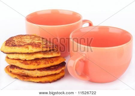 Pumpkin pancakes and two orange cups for breakfast isolated on white background