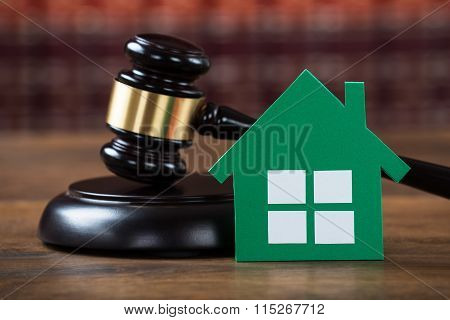 Mallet With Green Paper House In Courtroom