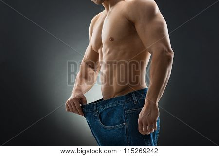 Midsection Of Muscular Man In Old Jeans Showing Weight Loss