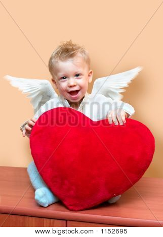 laughing cute angel boy with big plush red heart. copy space on the top right corner poster