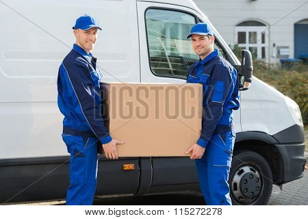 Delivery Men Carrying Cardboard Box Against Truck