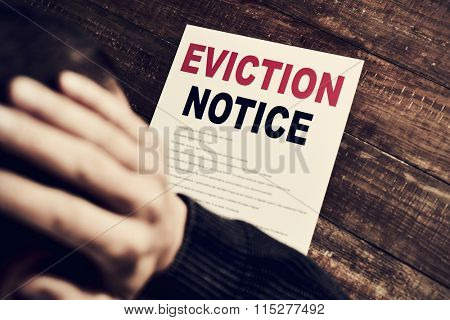 a young caucasian man with his hands in his head concerned because has just received an eviction notice