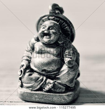 closeup of a laughing fat buddha in duotone
