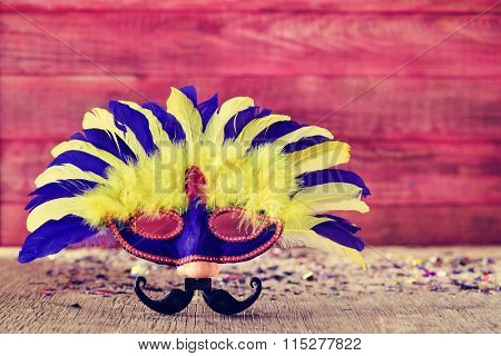 carnival mask ornamented with feathers of different colors and a fake nose and a fake mustache, on a rustic wooden surface full of confetti