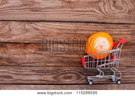 Shopping cart with rotten orange on the old wood background. Mold on food. The concept of selling sp