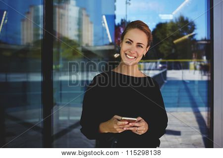 Young female employee using cell telephone and looking to the camera with nice smile