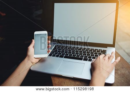 Female holding cell phone and keyboarding on net-book