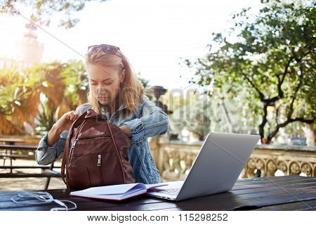 Hipster girl looking for something in the bag while sitting outdoors at the table with open net-book