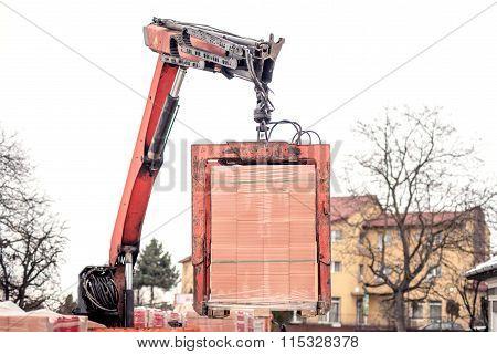 Crane Or Industrial Forklift Delivers A Brick Pallet At Building Construction Site