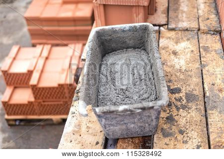 Mud pan with cement and mortar for bricklaying on construction site poster