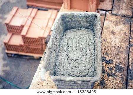 Mud Pan With Cement, Mortar And Tools For Bricklaying On Construction Site