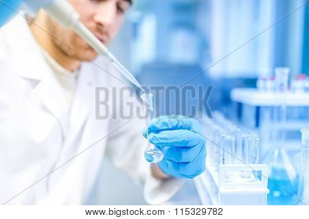 Male Scientist Using Medical Tool For Extraction Of Liquid From Samples In Special Laboratory