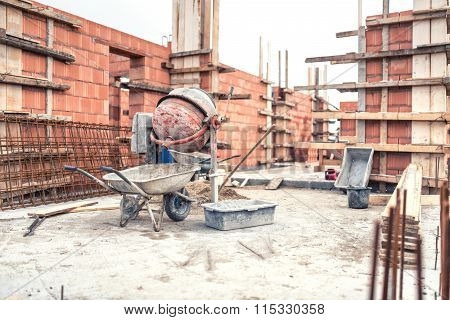 Cement Mixer Machine At Construction Site, Tools, Wheelbarrow, Sand And Bricks At New House Building