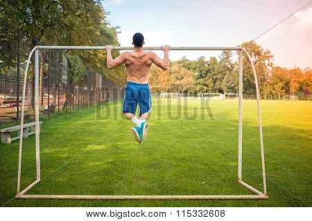 Young Muscular Man Doing Pull Ups On Football Court, Hardcore Training Outdoors