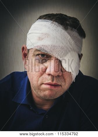 Man with a bandaged head and eye patch