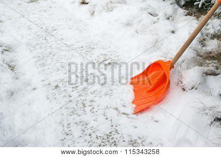 Snow removal. Orange Shovel in snow