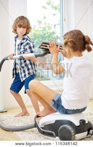 Two kids playing with vacuum cleaner while cleaning at home