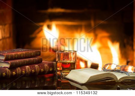 Glass of alcoholic drink wine and antique books in front of warm fireplace. Magical relaxed cozy atmosphere near  fire