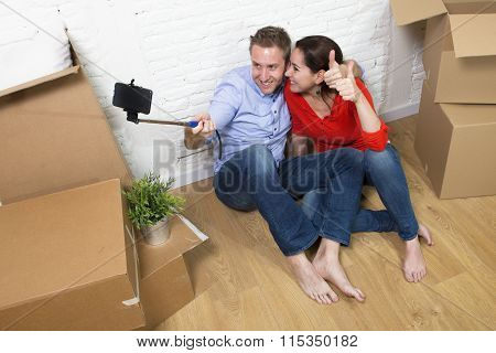 Young Happy American Couple Sitting On Floor Celebrating Moving In New House Taking Selfie Photo