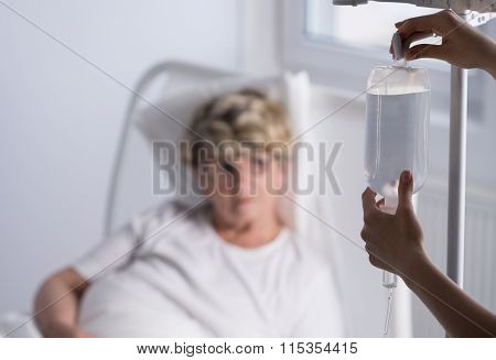 Nurse Changing A Drip Bag