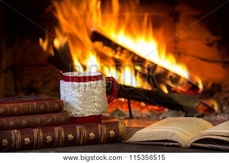 Cup of hot drink, antique books and fireplace as background. Christmas or winter warming drink.