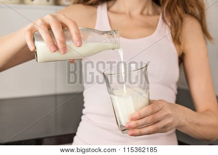 Woman Pouring Milk From A Bottle