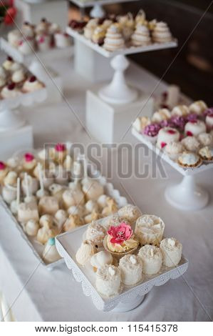 Wedding reception dessert table with delicious decorated white cupcakes with frosting closeup poster