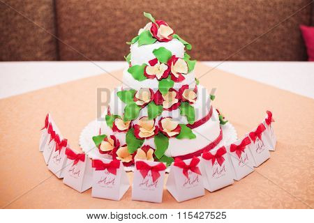 White Wedding Cake With Red Flowers On The Table