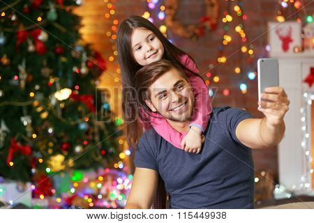 Older brother and little sister taking photo of their self with smart phone in Christmas living room