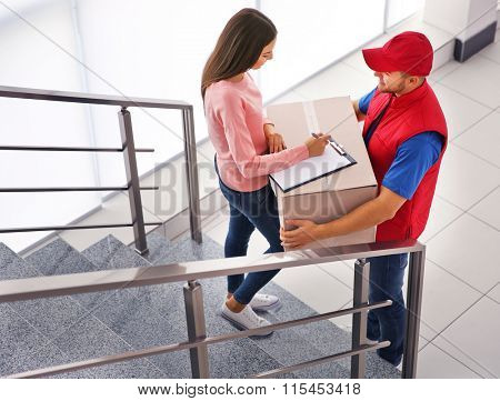 Young woman and courier on stairs - delivery concept