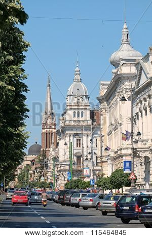 ARAD, ROMANIA - JULY 30, 2015: domes and bell tower of University Aurel Vlaicu, City Hall Palace and Evangelical Church along a busy Revolution Avenue of Arad.