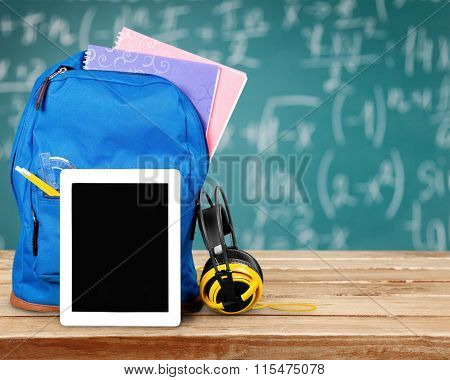 Blue School Backpack  and tablet pc on   background.