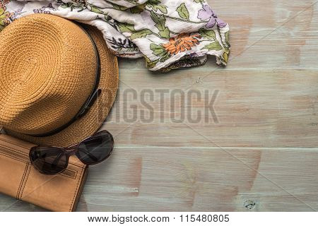 Travel summer vacation tourism and objects concept - close up of hat wallet sunglasses and scarf on wooden table. Top view with copy space.