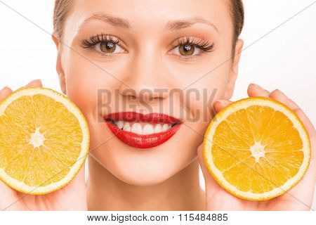 Girl and oranges. Young smiling attractive girl is upholding two halves of one orange beside her face.