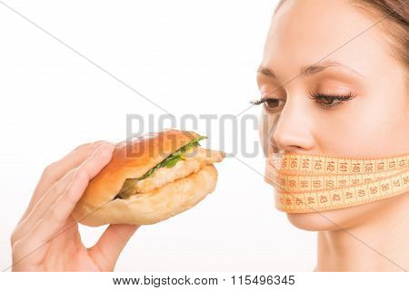 Young girl upholding a burger.