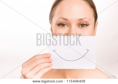 Young girl with smiley paper.