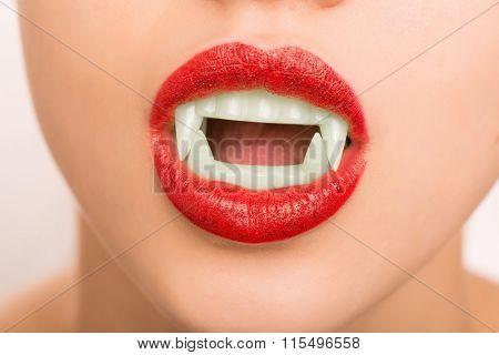 Young girl wearing make up and fake vampire teeth.
