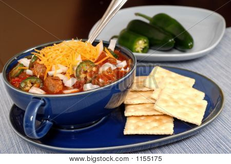 Bowl Of Spicey Chili And Crackers With Jalapeno Peppers