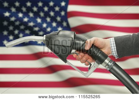 Fuel Pump Nozzle In Hand With National Flag On Background - United States - Usa
