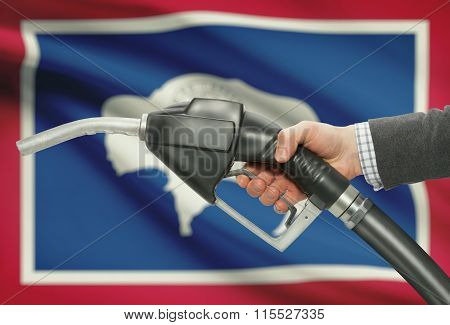 Fuel Pump Nozzle In Hand With Usa States Flags On Background - Wyoming