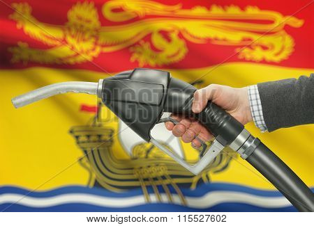 Fuel Pump Nozzle In Hand With Canadian Provinces Flags On Background - New Brunswick