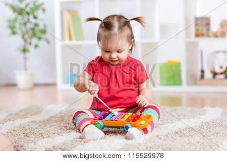 Child little girl plays a musical instrument xylophone