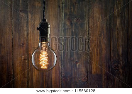 Vintage Incandescent Edison Type Bulb On Wooden Background