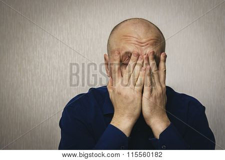 Man in depression, hands covered his face