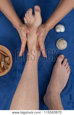 Feet Being Massaged By Female Therapist On Blue Towel