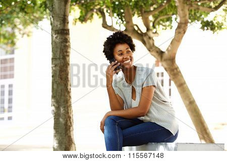 African Woman Relaxing On A Bench And Using Cell Phone