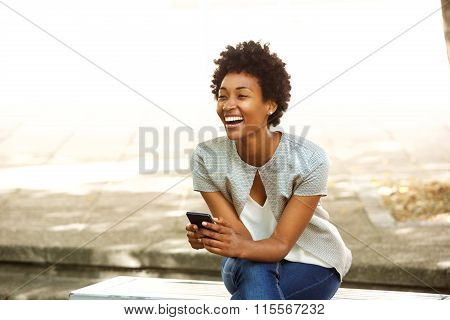 Beautiful Young African Woman Smiling Outside With Mobile Phone
