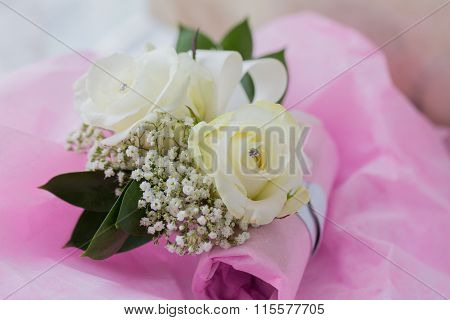 A Coloured Macro Photo Of Two Bridesmaids ' Flower Bracelets With One Fake Diamond In The Centre Of